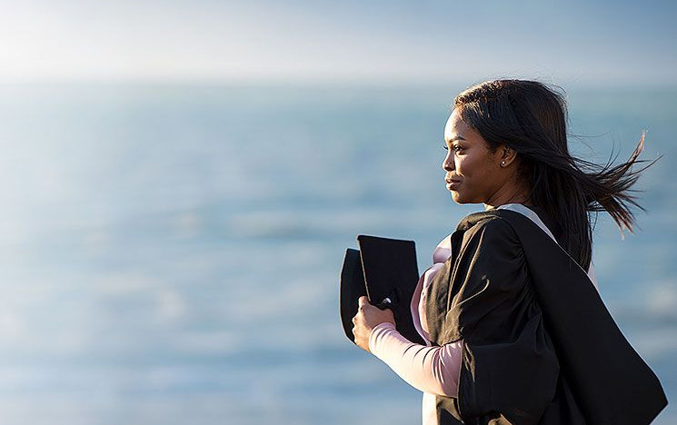 A windswept postgraduate student holding their mortarboard against a sea backdrop