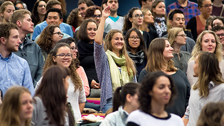 A student raising their hand in a crowd of other standing, engaged students