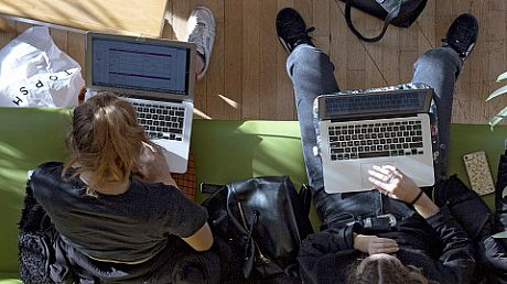 Two students working on laptops, from above