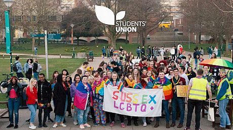 Students in Library Square holding LGBTQ banner