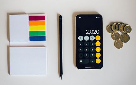 Calculator on phone next to pile of coins